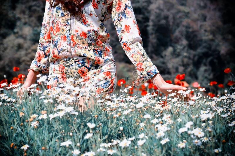 Women in the garden. Women in walk and pat flower in the garden royalty free stock image