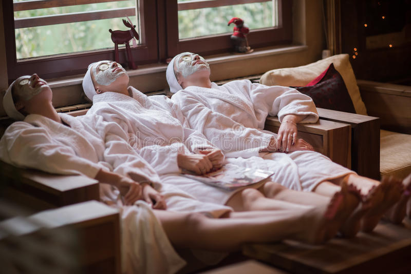 Women is getting facial clay mask at spa stock photos