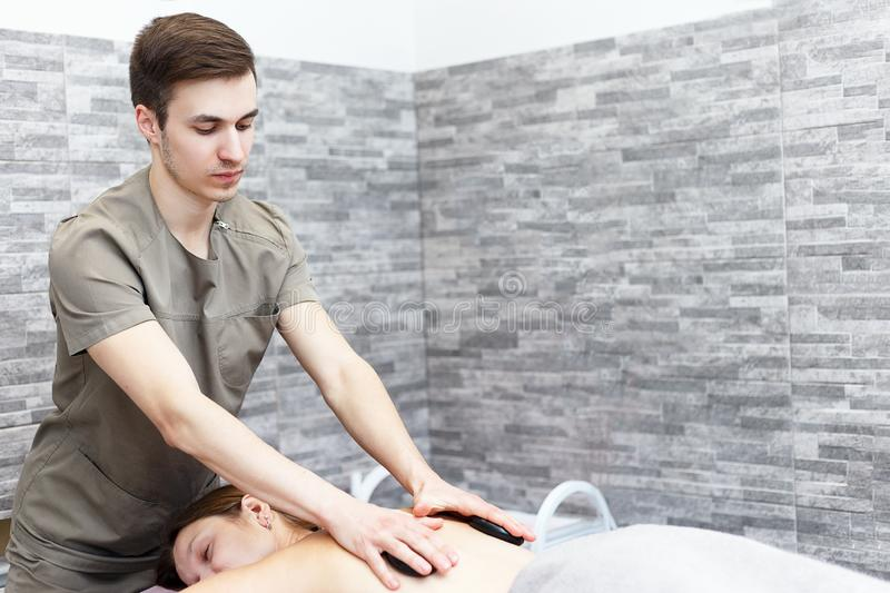 A woman is getting a hot stone massage at a spa stock photography