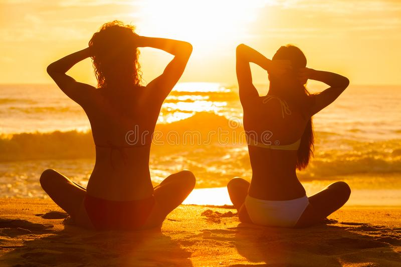 Women Girls Sitting Sunrise Sunset Bikini Beach. Saturated, stylised view of two relaxed young women or girls wearing a bikini sitting on a deserted tropical stock photography