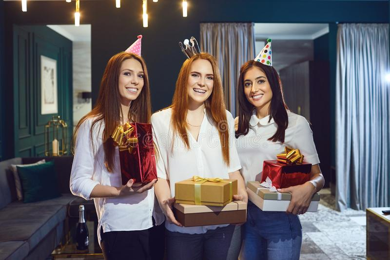 Women giving birthday presents to friend. Cheerful women congratulating friend on birthday and giving gift boxes gathering at home royalty free stock photography