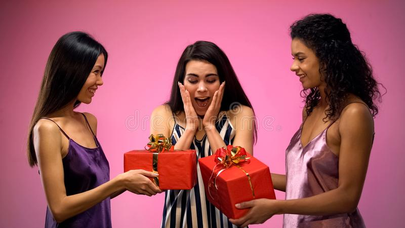 Women giving present to surprised friend, all-girl birthday party, emotions stock images