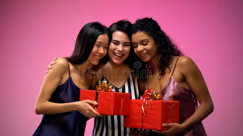 Women giving presents to friend and hugging, having fun at bridal shower, joy stock photo