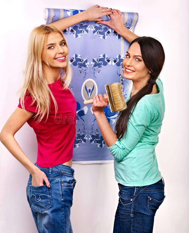 Women glues wallpaper at home. Happy women glues wallpaper at home stock image