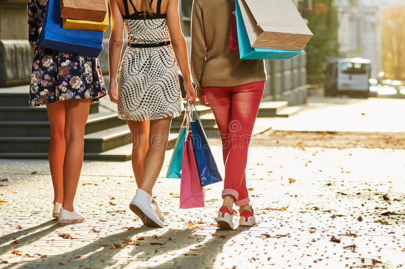 Women Going Legs. Girls women friends with legs walking. from back. with shopping bags royalty free stock photo