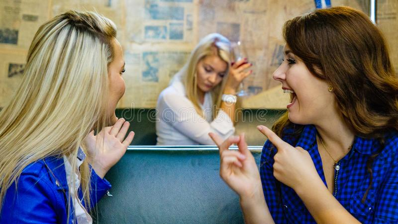 Women gossiping about friend. Women two girlfriends gossiping about third, sad girl with alcohol glass in the background. Friendship rivaly and envy problems stock images