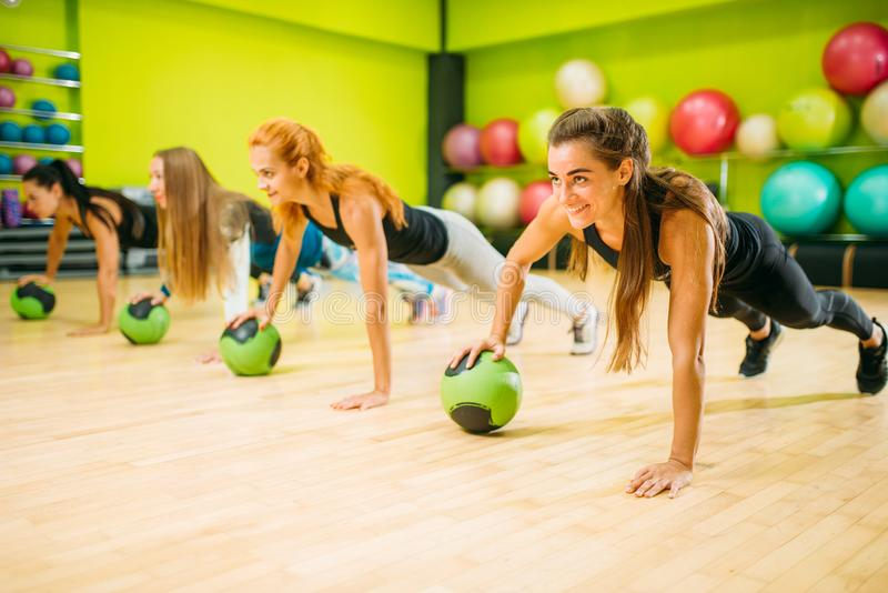 Women group with balls doing push up exercise royalty free stock photography