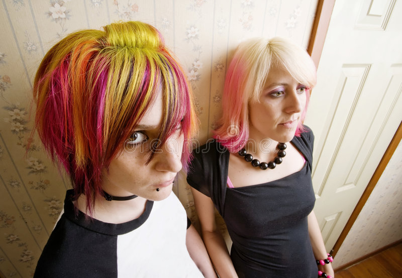 Women in a Hallway. Women in colorful hair leaning a wall in a hallway royalty free stock photography