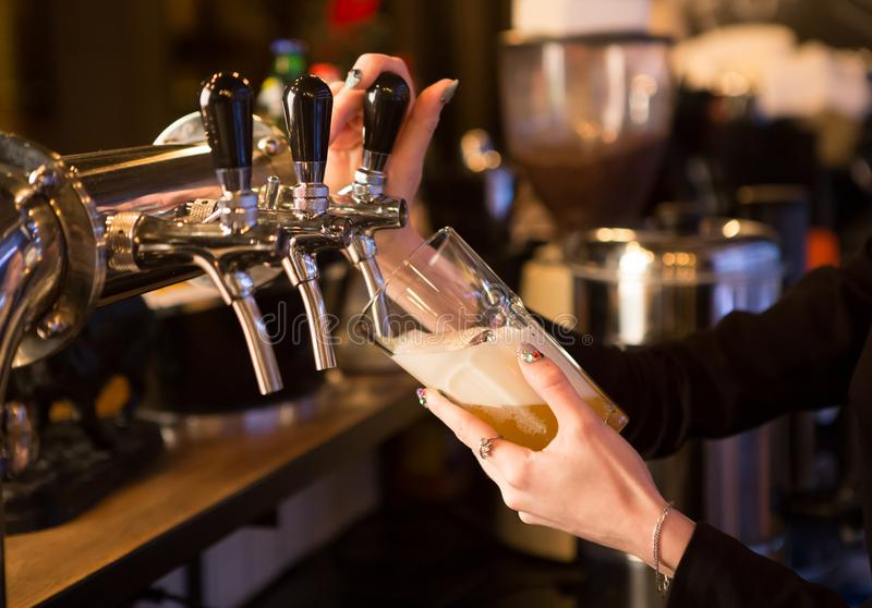 Beer pouring at bar. Women hand holding beer glass and pouring beer from tap stock photos