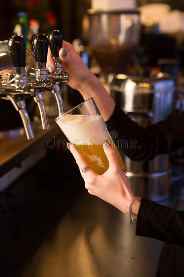 Beer pouring at bar. Women hand holding beer glass and pouring beer from tap royalty free stock photos