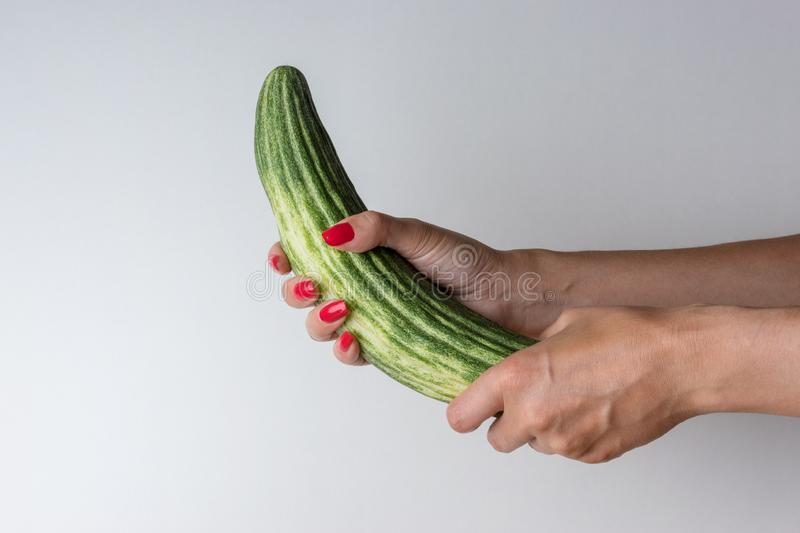 Women hand holding cucumber like a man`s penis on white background. Erotic concept.  stock images