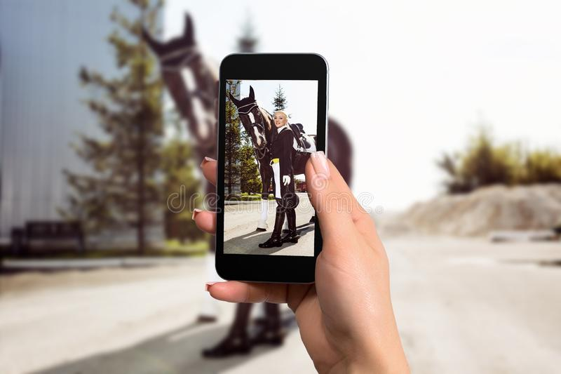 Women hand holding mobile smartphone taking picture of woman rider with a horse. stock photos