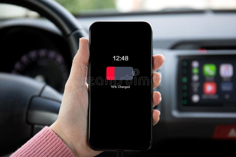 Women hand holding phone with low charged battery on screen. In the car stock photography