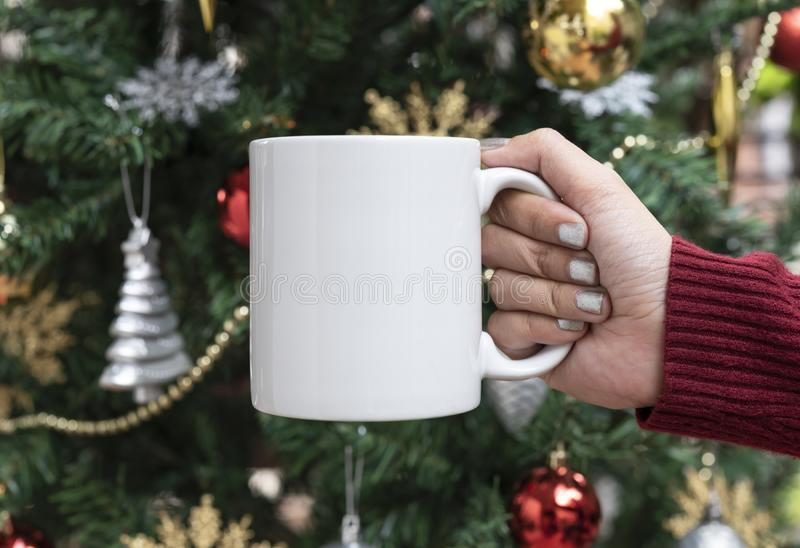 Women hand holding white ceramic coffee cup on christmas tree background. mockup for creative advertising text message or royalty free stock photo