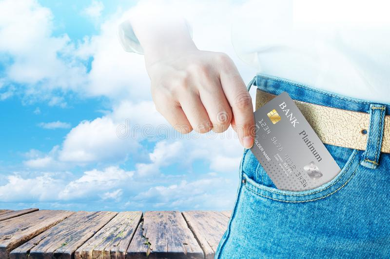 Women hand pick up realistic credit or debit card with old wood table on cloud sky background royalty free stock photo