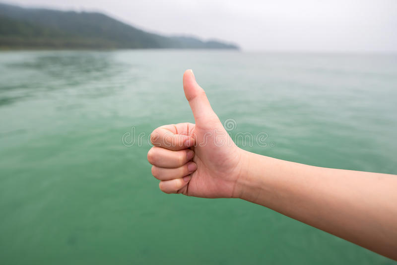 Women hand with thumb up on green sea. Background,soft focused stock image