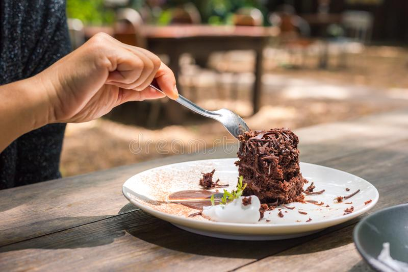 Women hand using a stainless spoon to eat chocolate cake,Relax time with enjoy eat Dessert. Women hand using a stainless spoon to eat chocolate cake royalty free stock image