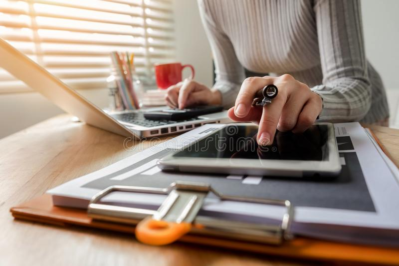 Women hand working with laptop computer, tablet in modern office stock images