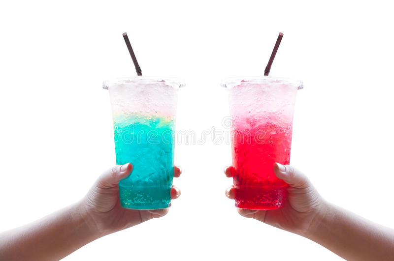 Women handle holding ice water italian soda red and blue in plastic cup. Isolated on white royalty free stock photography