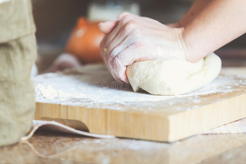 Women hands crumpling piece of dough on board. Women hands knead the dough piece on the board with flour. Side view royalty free stock images