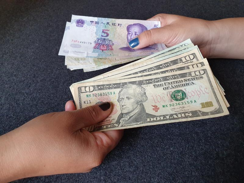 Women hands exchanging American dollar banknotes and Chinese money. Commerce, exchange, travel, trade, trading, value, buy, sell, profit, price, rate, cash stock image