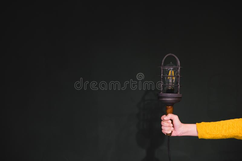 Women hands holding a vintage electric lamp in a metal grid lamp royalty free stock photo