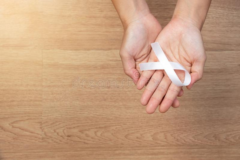 women hands holding white bow, white ribbons on wooden background. Awareness White ribbon for campaign to end violence against royalty free stock images