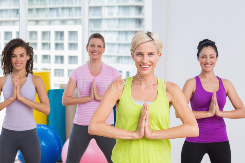 Women with hands joined exercising at gym. Portrait of happy fit women with hands joined exercising at gym royalty free stock images