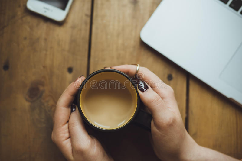 Women Hands with laptop and Coffee on the Table Top View royalty free stock photo