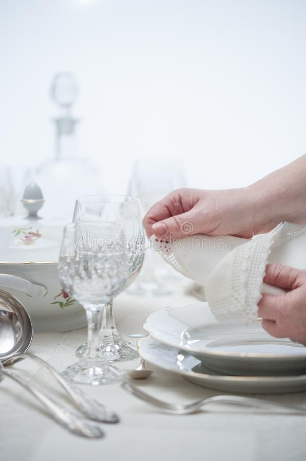 Women hands placing vintage lace napkins on a porcelain dish . S. Elective focus royalty free stock photography