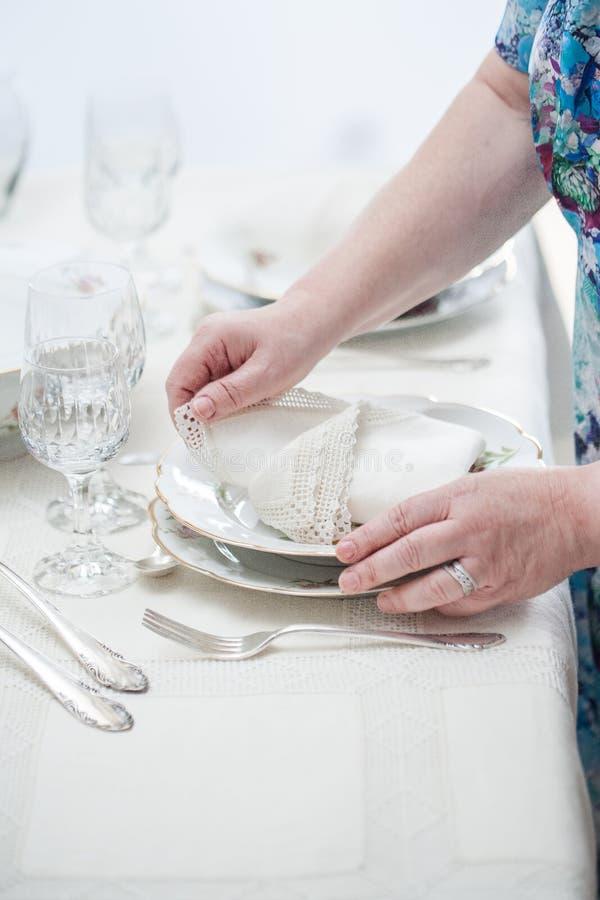 Women hands placing vintage lace napkins on a porcelain dish . S. Elective focus royalty free stock images