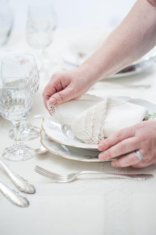 Women hands placing vintage lace napkins on a porcelain dish . S. Elective focus stock image