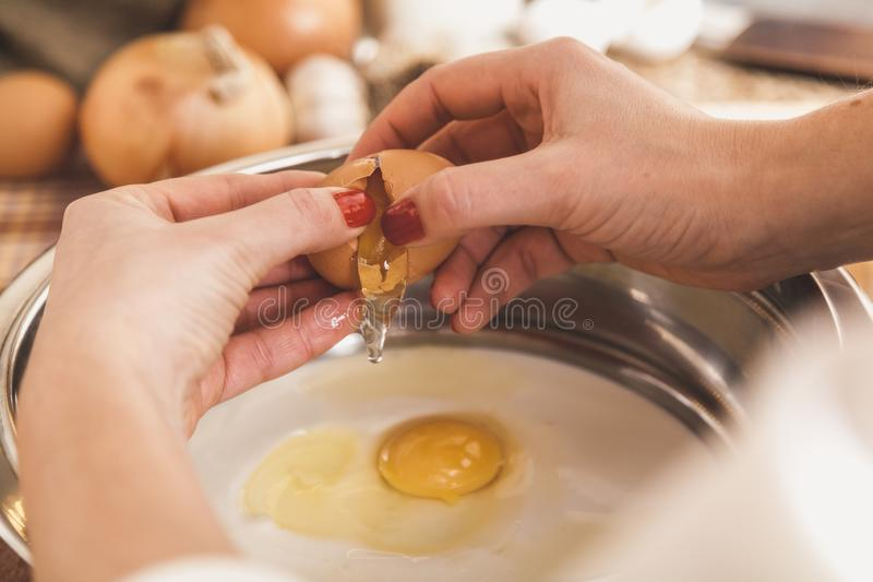 Women hands are separated egg over bowl. Women hands are separated broken egg over a bowl with the egg yolk stock photography