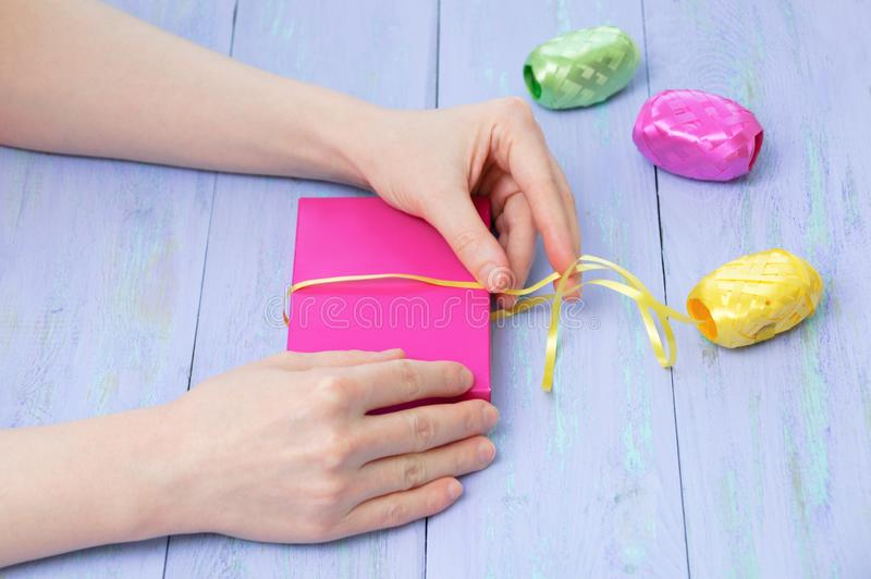 Women hands wrapped in a pink gift box with a yellow ribbon violet wooden background. Cose-up stock photo