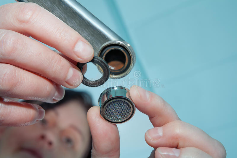 Women handyman replace tap aerator, plumber hand close-up. royalty free stock photography