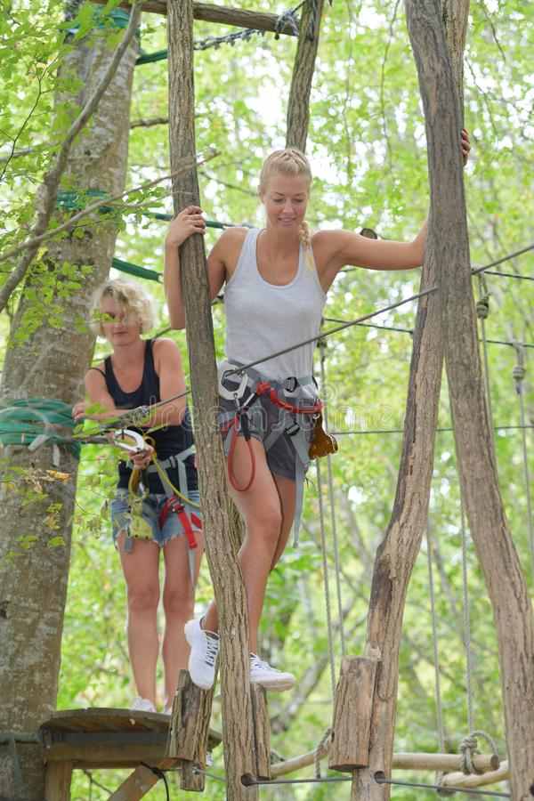 Women hanging on rope for adventure activity. Female stock images