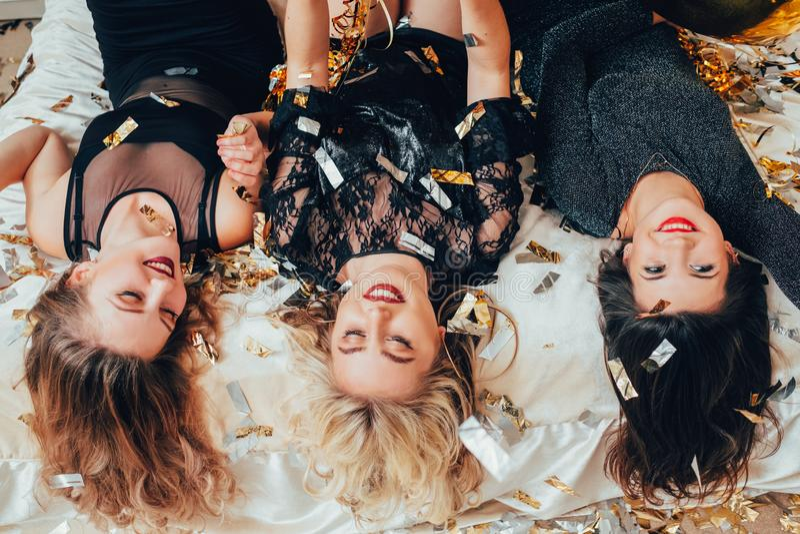 Women hangout joy lying upside down confetti stock photo