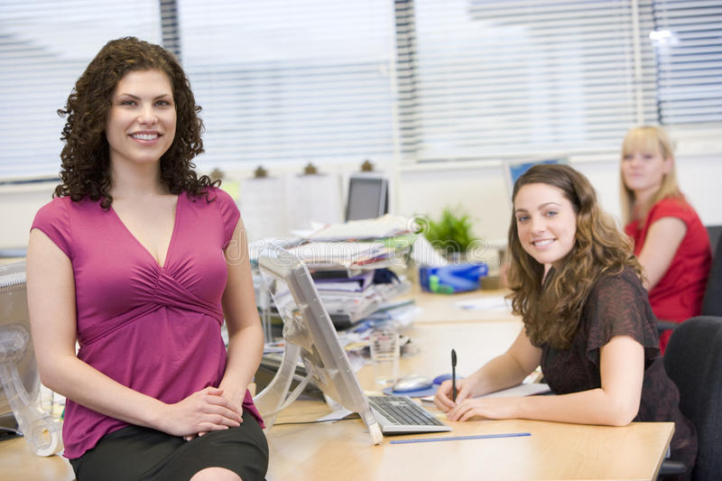 Women happily working in an office stock image