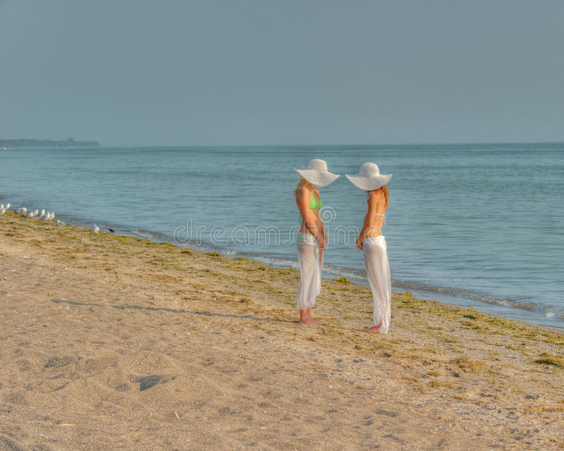 Women in hats. Two women in bikinis standing on beach in white hats stock photography