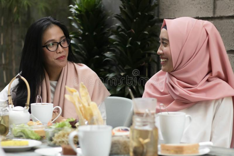 Women having conversation in middle of lunch stock photo