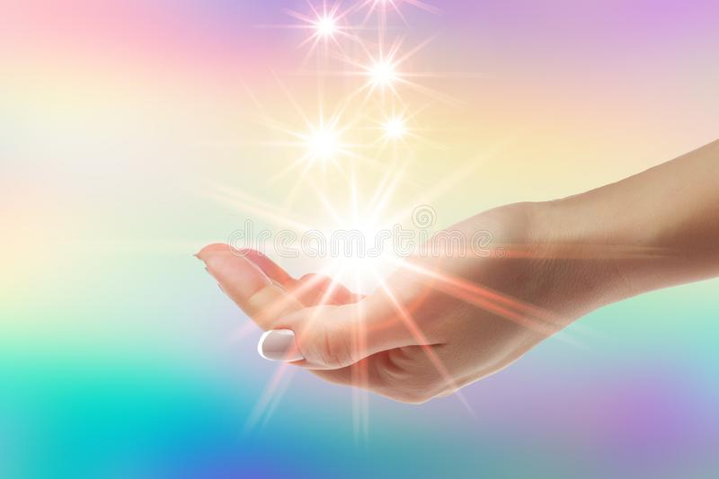 Healing hands with bright sunburst on rainbow background. Women healing hands with bright sunburst on rainbow background stock photos
