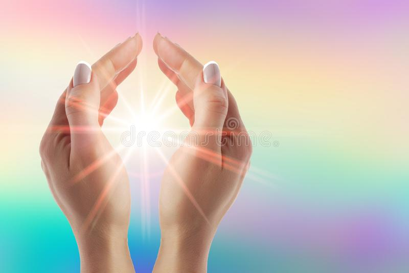 Healing hands with bright sunburst on rainbow background. Women healing hands with bright sunburst on rainbow background royalty free stock photos