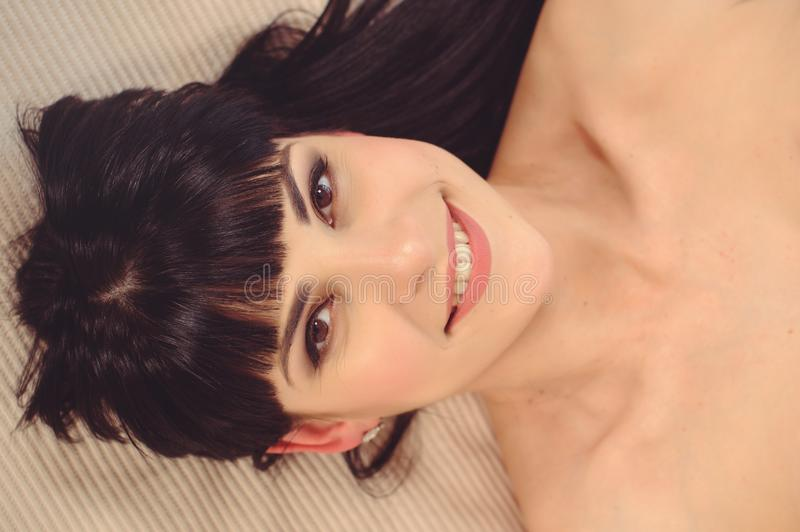 Women Health. Closeup portrait of beautiful smiling woman with fresh face, soft skin, lying on bed with pleasure. Healthy happy royalty free stock image