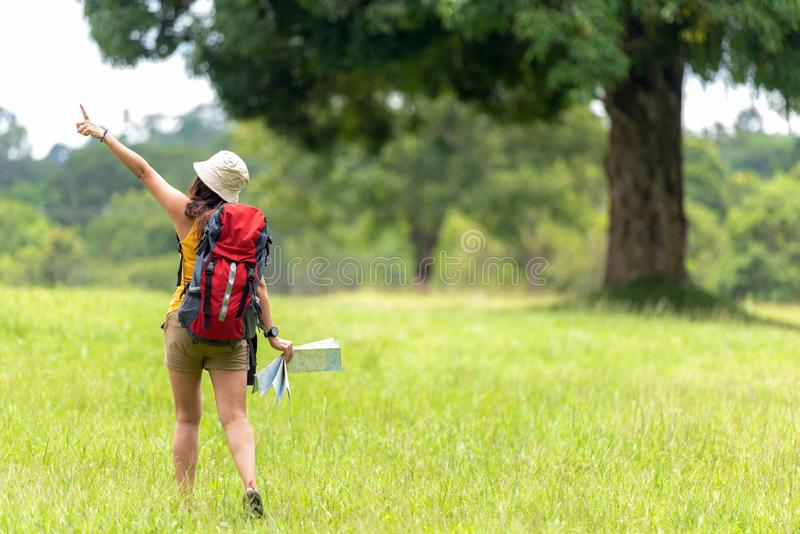 Women hiker or traveler with backpack adventure holding map to find directions and walking relax in the jungle forest outdoor for royalty free stock photos
