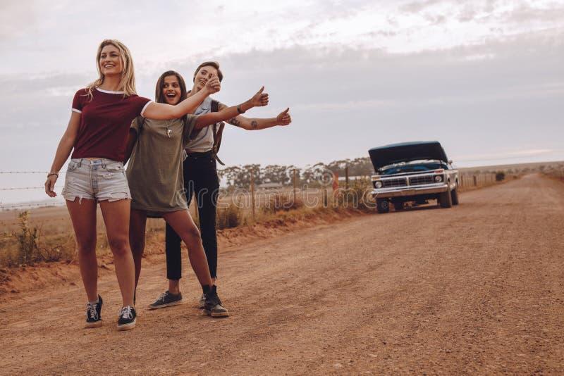 Women hitchhiking near their broken car on country road. Three young women hitchhiking near their broken car on country road. Smiling female friends gesturing stock photos
