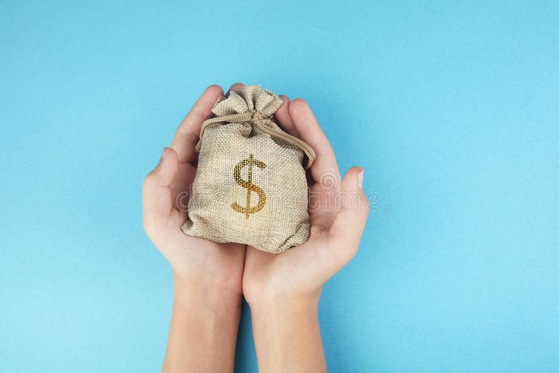 Women hold a money bag on blue background, Saving money for future investment concept. Women hold a money bag on light blue background, Saving money for future stock photo
