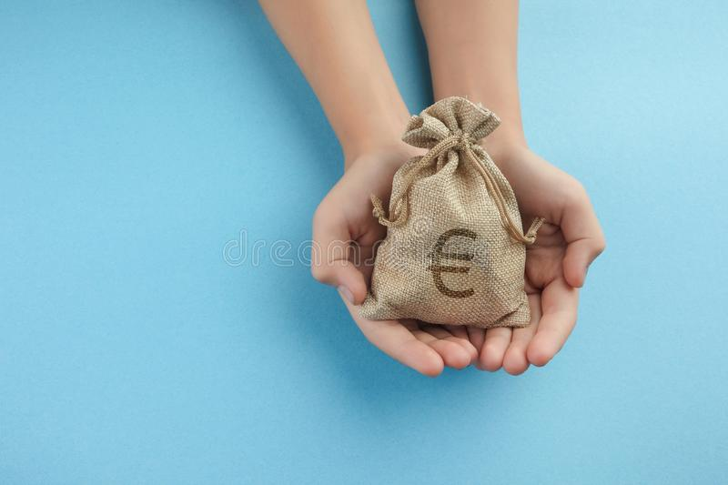 Women hold a money bag on blue background, Saving money for future investment concept. Women hold a money bag on light blue background, Saving money for future royalty free stock photos