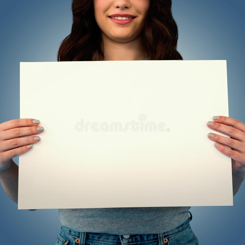 Composite image of women holding blank poster. Women holding blank poster against purple vignette stock photography