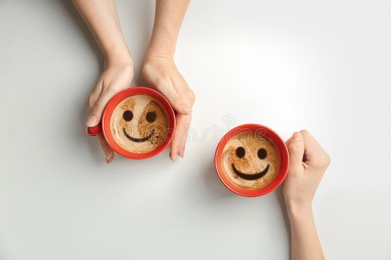 Women holding cups of delicious hot coffee with foam and smiles on light background, top view. royalty free stock image