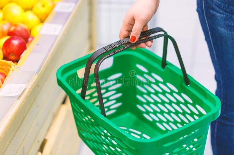 Women holding empty green shopping basket near fruits window in the supermarket. Shopping concept stock photography